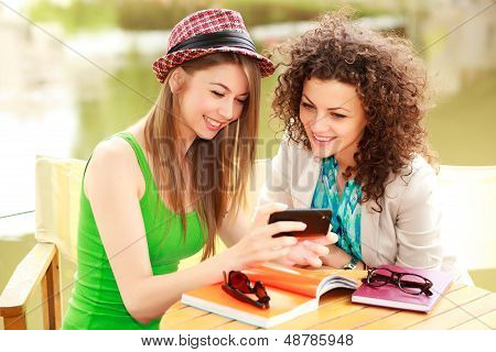 Two Beautiful Women Playing On A Smart-phone And Chatting On The River Side Terrace