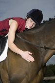 Portrait of a female horseback rider hugging a cropped brown horse poster