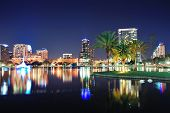 Orlando downtown skyline panorama over Lake Eola at night with urban skyscrapers, tropic palm tree and clear sky. poster