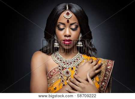 Young Indian woman dressed in traditional clothing with bridal makeup and jewelry poster