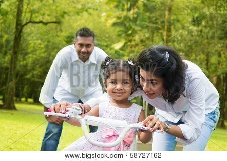 Indian family outdoor activity. Asian parent teaching child to ride a bike at the park in the morning.