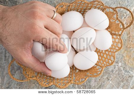 Man Taking An Egg From An Easter Basket