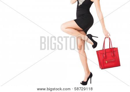 woman body in short black dress, high heel shoes hold in hand red handbag