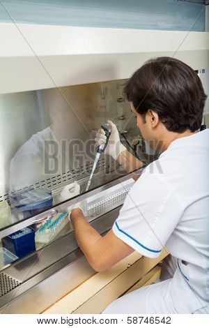 Male researcher filling solution in test tube at laboratory