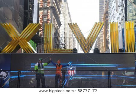 Seattle Seahawlks and Denver Broncos fans posing for picture next to Roman Numerals on Broadway