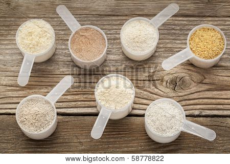 top view of measuring scoops of gluten free flours - almond, coconut, teff, flaxseed meal, whole rice, brown rice, buckwheat