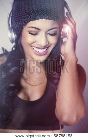 Beautiful young woman wearing beanie hat headphones happy listening to the beat of music
