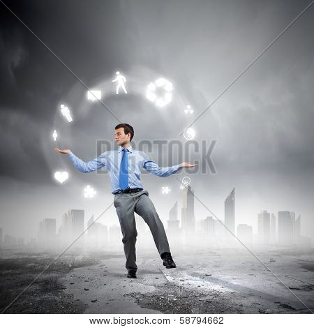 Young businessman juggling with conceptual symbols against city background poster