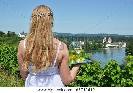 Girl holding wine and grapes against Rhine rive in Rheinau, Switzerland