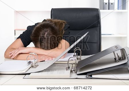 Young Frustrated Woman Is Lying In Front Of A Pile Of Files