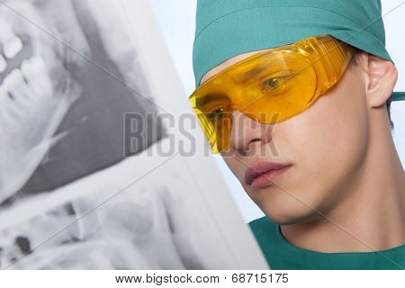Young doctor dentist with jaw xray on blue background