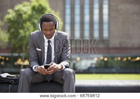 Portrait of African American Businessman listening to music with headphones outdoors poster