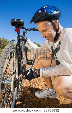 Smiing cyclist fixing his bike chain on country terrain on a sunny day