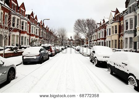 Snow cityscape of a terraced street in London England with slippery blizzard conditions showing cars covered with ice and a blanket of snow poster