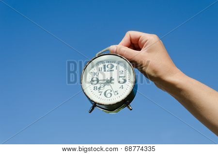 Hand Hold Clock With Big Numeral On Sky Background