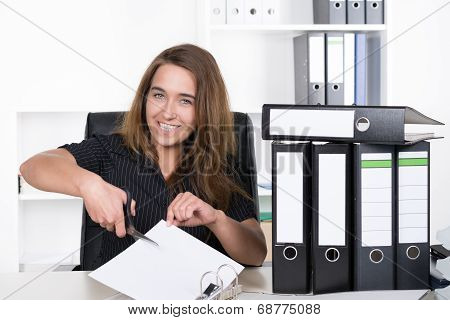 Young Woman Is Cutting A Sheet Of Paper With A Pair Of Scissors
