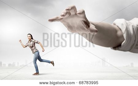 Young woman in casual escaping from big male hand poster