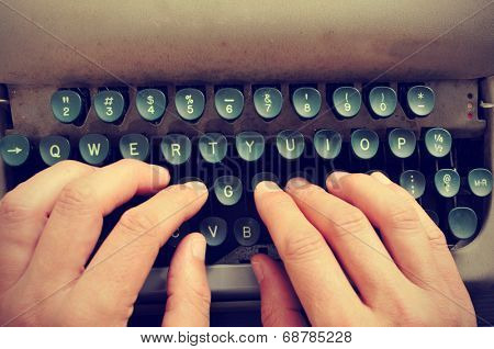 closeup of the hands of a man typing on an old typewriter