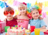 Three kids are happily posing during birthday party poster