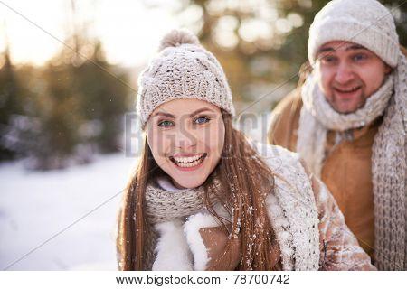 Cute girl in winterwear looking at camera on background of her boyfriend in winter park