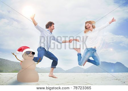 Festive sandman against cheerful couple holding hands and jumping at beach