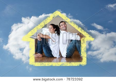 Radiant couple with unpacking boxes moving to a new house against cloudy sky