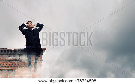 Frustrated businessman on building top closing ears with hands