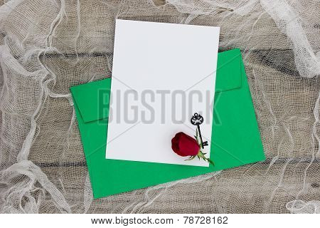 Blank white letter and envelope with red rose and key on shabby netting background