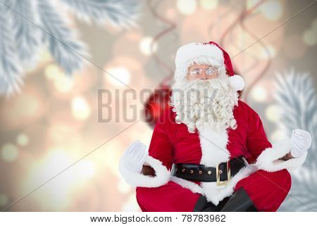 Santa claus sitting in lotus pose against digital hanging christmas bauble decoration