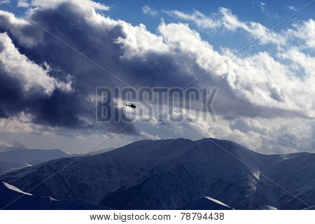 Helicopter In Cloudy Sky And Winter Mountains In Evening