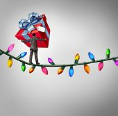 Holiday risk concept as a person holding a giant gift on a high wire tightrope made from christmas lights as a debt and credit metaphor and symbol of the challenges of giving. poster