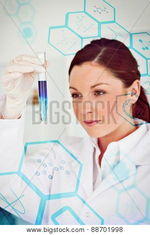 Medical interface against beautiful redhaired scientist looking at the camera while holding a test tube