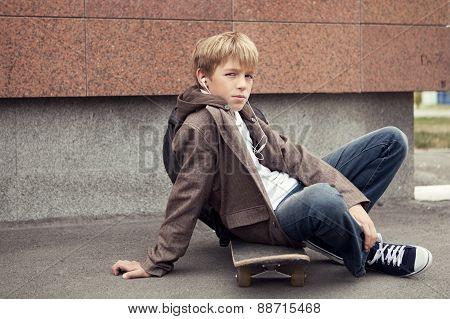 School Teen Sits On Skateboard Near School