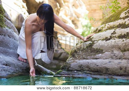 Beautiful girl taking water from stream-let