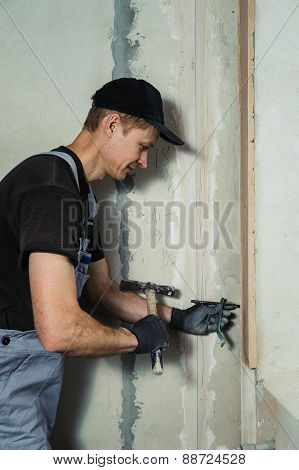 Woker Hammers A Nail With A Foot Into A Wall