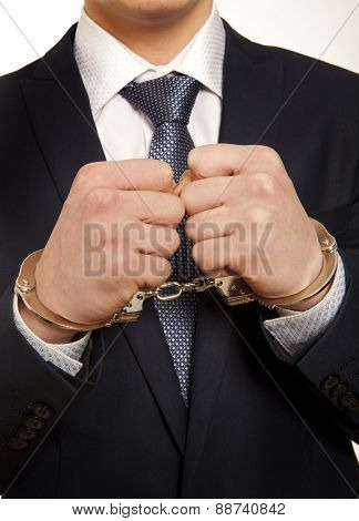 Arrested business man handcuffed hands. Close-up.   poster