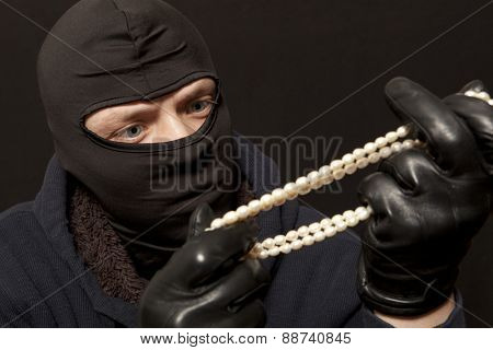 Thief. Man in black mask with a pearl necklace. Focus on thief poster