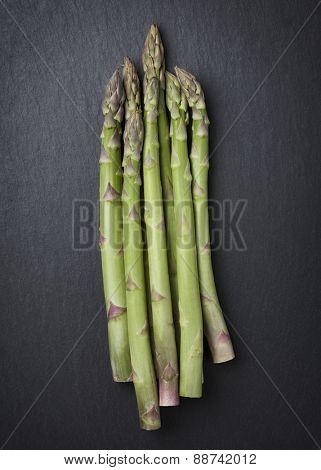 Group of organic asparagus isolated on dark gray slate stone slab.