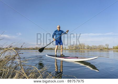 Senior male on stand up paddling (SUP) board. Early spring on calm lake in Colorado.