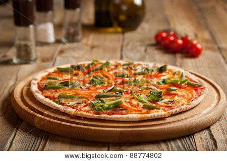 "Italian pizza ""Vegetarian"" on wooden table. On top of the pizza are baked sliced tomatoes and asparagus broccoli. Nearby are containers with spices and olive oil. Near them are cherry tomatoes. poster"