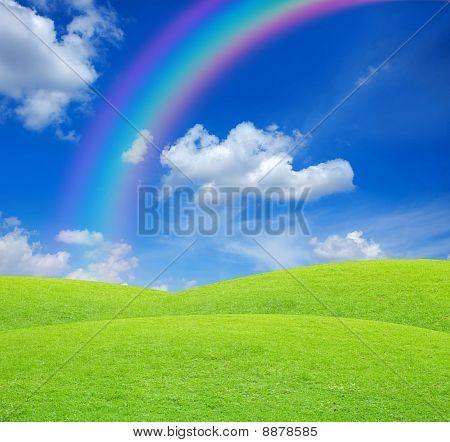 Green Field On Blue Sky With Rainbow