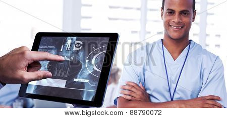 Man using tablet pc against smiling doctor with arms crossed