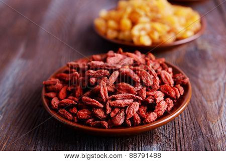 Raisins and Goji in small plates on rustic wooden table background