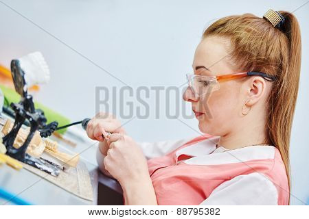 Female dental technician working with tooth dentures at prosthesis laboratory