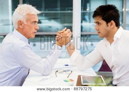 Two businessmen competeting arm wrestling in office