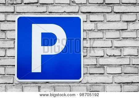 Blue Parking Sign On Black And White Bricks