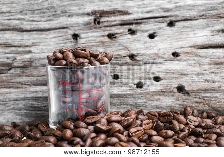 Roasted coffee beans in coffee shot glass and around with wood background