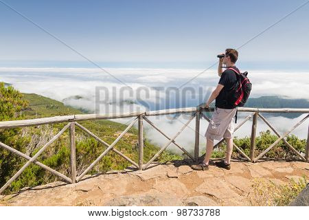 Man Looking Into Binoculars In Madeira Viewpoint