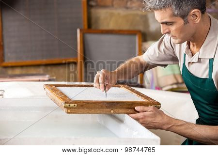 Mature male worker cleaning paper with tweezers over vat in factory poster