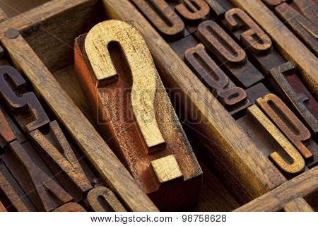 question mark - vintage wooden letterpress type block in old typesetter drawer among other letters stained by color inks